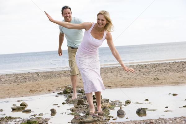 Couple at the beach walking on stones and smiling Stock photo © monkey_business