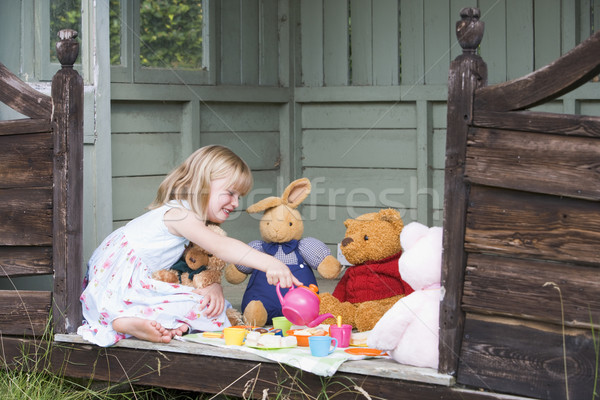 Stock photo: Young girl in shed playing tea and smiling