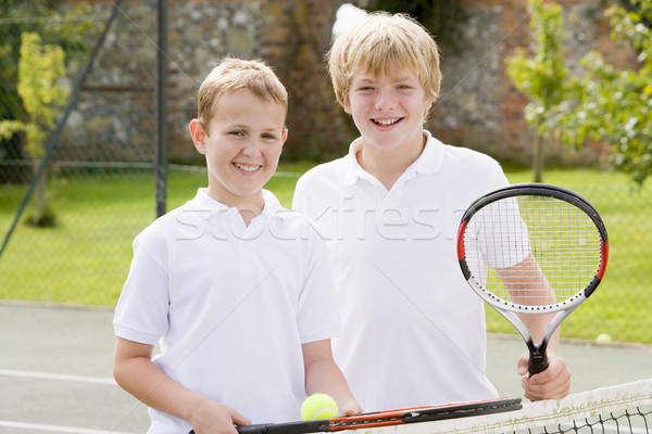 Two young male friends with rackets on tennis court smiling Stock photo © monkey_business