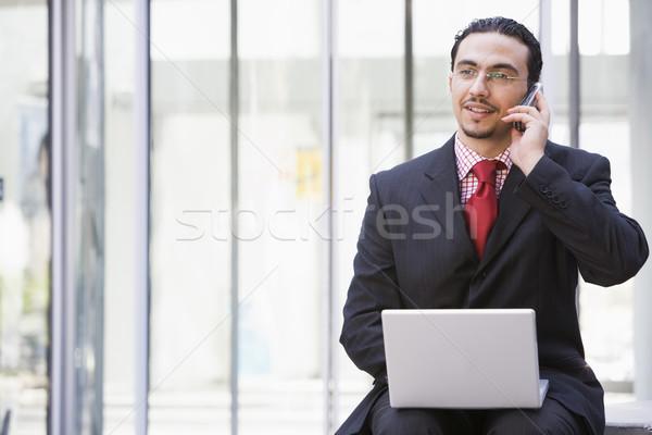 Сток-фото: бизнесмен · используя · ноутбук · мобильного · телефона · за · пределами · компьютер · служба