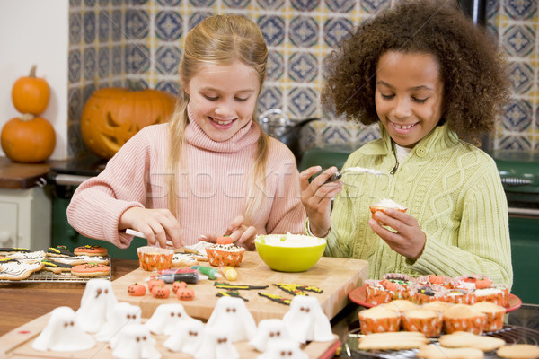 Two young girl friends at Halloween making treats and smiling Stock photo © monkey_business