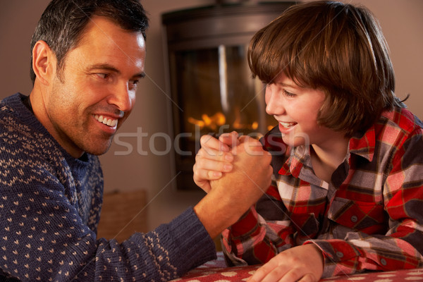Father And Son Arm Wrestling By Cosy Log Fire Stock photo © monkey_business