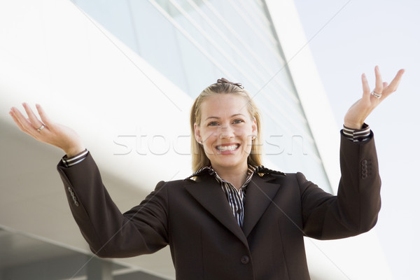 Businesswoman standing outdoors by building smiling with hands o Stock photo © monkey_business