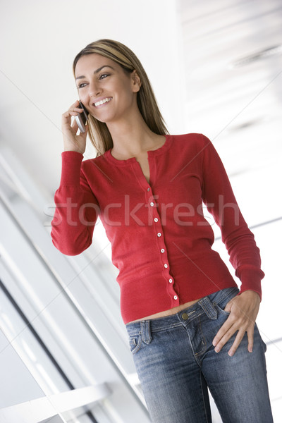 Woman standing in corridor using cellular phone smiling Stock photo © monkey_business