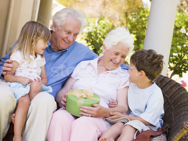 Grandparents with grandchildren on patio with gift smiling Stock photo © monkey_business