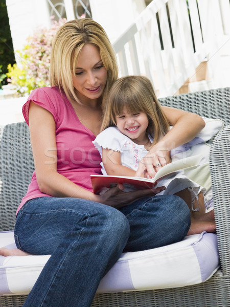 Woman and young girl sitting on patio reading book smiling Stock photo © monkey_business