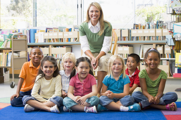 Stock photo: Kindergarten teacher sitting with children in library