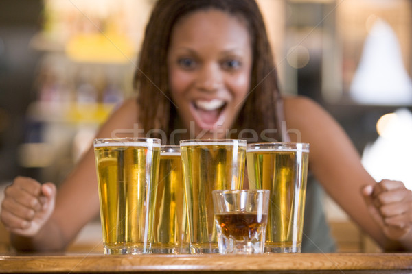 Young woman staring excitedly at a round of beers Stock photo © monkey_business