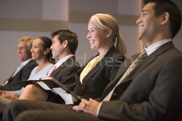 Five businesspeople smiling in presentation room with clipboards Stock photo © monkey_business