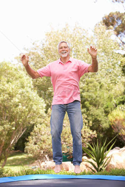 Senior Man Jumping On Trampoline In Garden Stock photo © monkey_business