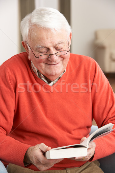 Senior Man Relaxing In Chair At Home Reading Book Stock photo © monkey_business