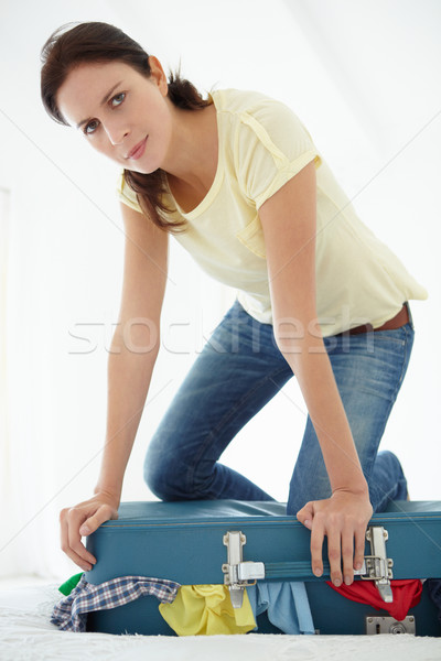 Woman struggling to close suitcase Stock photo © monkey_business