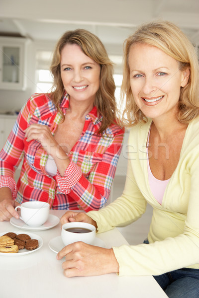 Mid age women chatting over coffee at home Stock photo © monkey_business