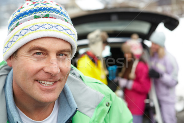 Father Smiling At Camera Whilst Family Load Skis In Boot Of Car Stock photo © monkey_business