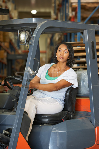 Woman Driving Fork Lift Truck In Warehouse Stock photo © monkey_business