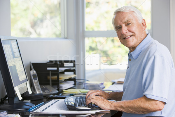 Stock photo: Man in home office using computer smiling