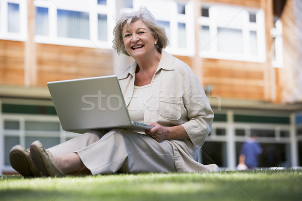 Stock photo: Senior woman using laptop on campus