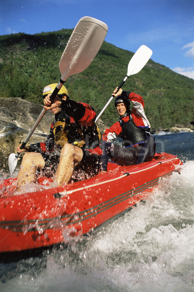 Stock photo: Two people paddling inflatable boat down rapids