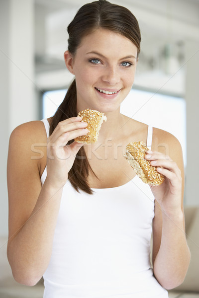 Stock photo: Young Woman Eating Brown Bread Roll
