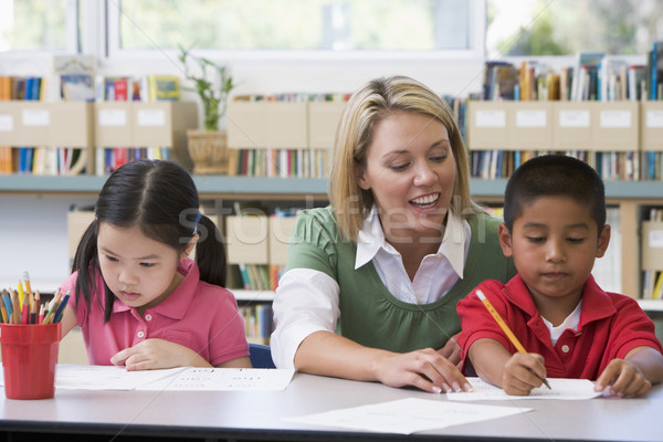 Stock photo: Kindergarten teacher helping students with writing skills