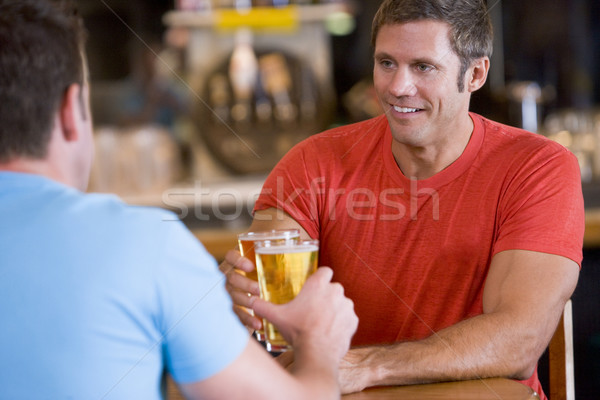 Two men toasting beer in a bar Stock photo © monkey_business