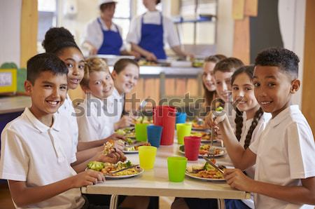 A teacher eating lunch with his students in the school cafeteria Stock photo © monkey_business