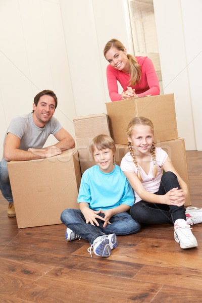 Young family on moving day looking happy among boxes Stock photo © monkey_business