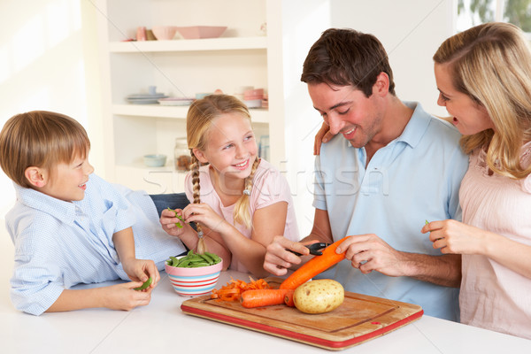 Happy family peeling vegetables in kitchen Stock photo © monkey_business