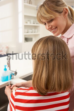 Mother And Daughter Washing Hands At Kitchen Sink Stock photo © monkey_business
