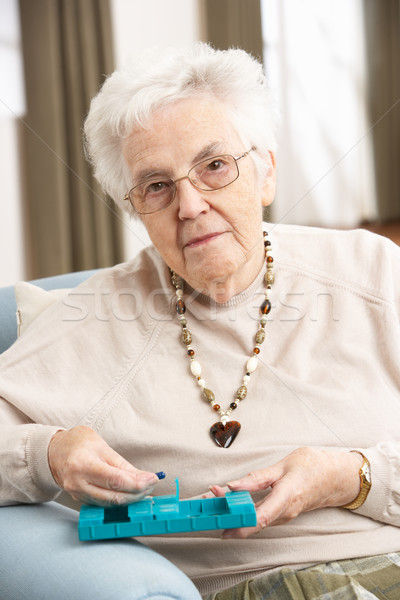 Senior Woman Sorting Medication Using Organiser At Home Stock photo © monkey_business