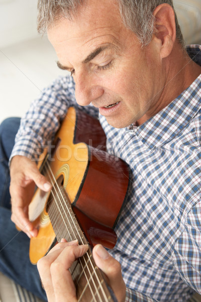 Mid age man playing acoustic guitar Stock photo © monkey_business