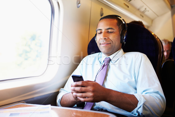 Businessman Relaxing On Train Listening To Music Stock photo © monkey_business