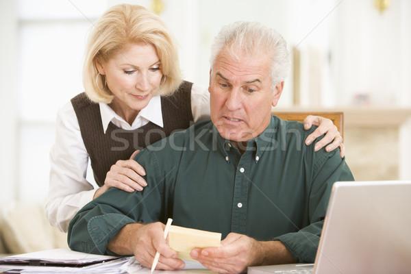 Casal sala de jantar laptop papelada olhando preocupado Foto stock © monkey_business