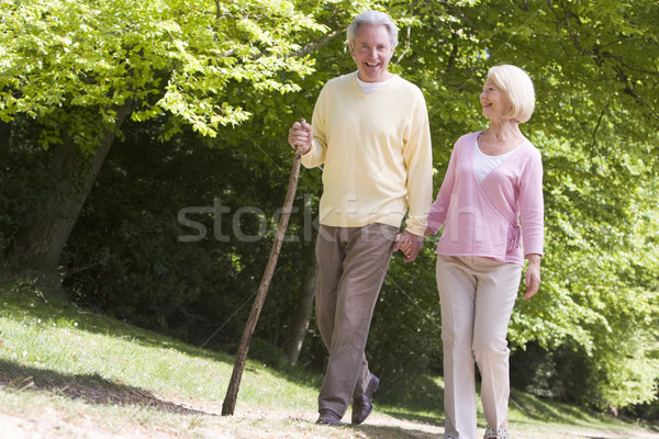 Couple walking on path in park holding hands and smiling Stock photo © monkey_business