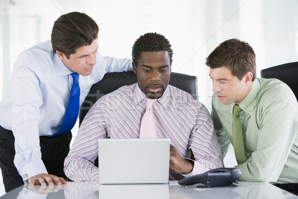 Three businessmen in a boardroom looking at laptop Stock photo © monkey_business