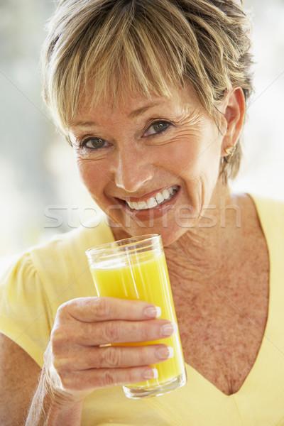 Foto stock: Mulher · sorrindo · câmera · potável · suco · de · laranja · mulher · casa