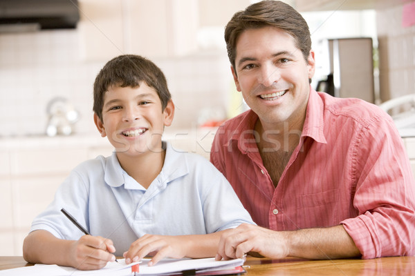 Man helping young boy in kitchen doing homework and smiling Stock photo © monkey_business