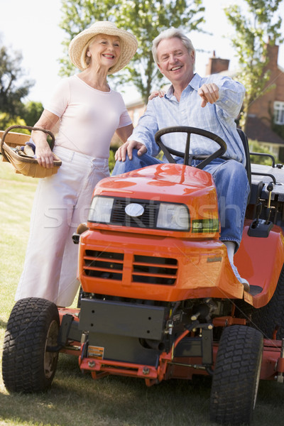 Couple outdoors with tools and lawnmower pointing and smiling Stock photo © monkey_business
