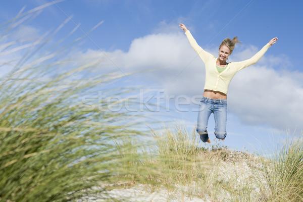 Young woman jumping amongst dunes Stock photo © monkey_business