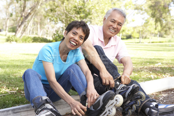 Senior Couple Putting On In Line Skates In Park Stock photo © monkey_business