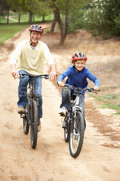 Grandfather and grandson riding bicycle in park Stock photo © monkey_business