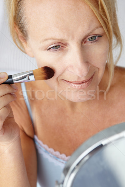 Mid age woman putting on make-up Stock photo © monkey_business