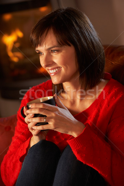 Middle Aged Woman Relaxing With Hot Drink By Cosy Log Fire Stock photo © monkey_business