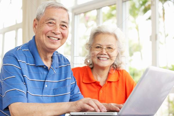 Senior Chinese Couple Sitting At Desk Using Laptop At Home Stock photo © monkey_business