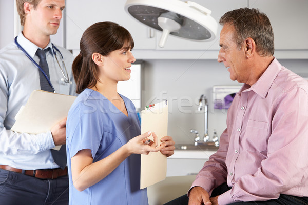 Male Patient Being Examined By Doctor And Intern Stock photo © monkey_business