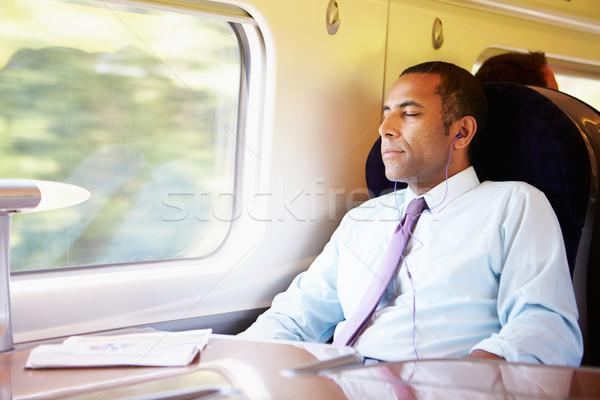 üzletember megnyugtató vonat zenét hallgat férfiak öltöny Stock fotó © monkey_business