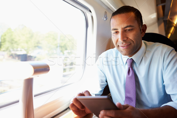 Businessman Commuting On Train Reading E Book Stock photo © monkey_business