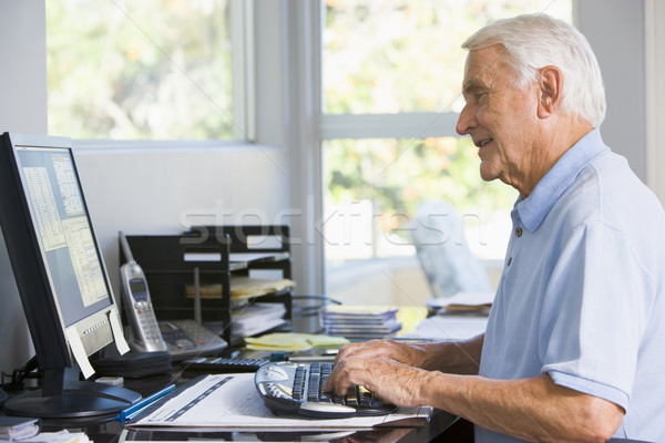 Man in home office using computer smiling Stock photo © monkey_business