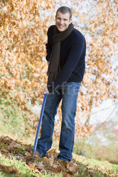 Young man clearing autumn leaves Stock photo © monkey_business