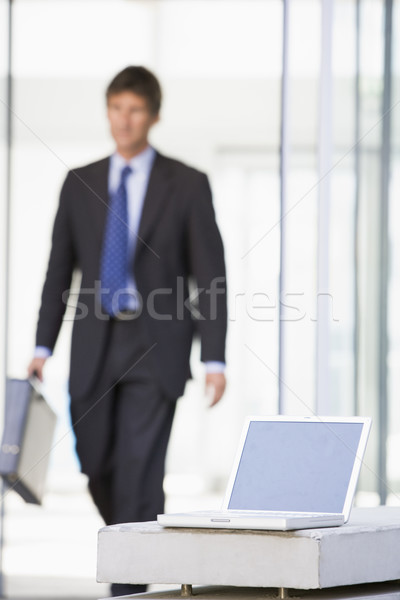 Laptop sitting in office lobby with businessman walking in Stock photo © monkey_business